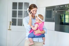 Woman talking on cellphone while carrying baby girl Stock Photography