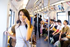 Woman talking on cellphone inside train compartment royalty free stock image