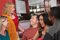 Woman Talking with Diverse Group. European lady talking with diverse group of people in a bistro Stock Photo
