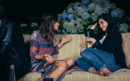 Woman talking with female friend in a party. Young women talking with female friend sitting on sofa in a outdoors party. Friendship and celebrations concept Royalty Free Stock Images