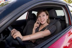 Woman talking happy on mobile phone while holding car steering wheel driving distracted Royalty Free Stock Images