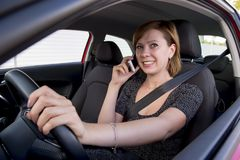 Woman talking happy on mobile phone while holding car steering wheel driving distracted Royalty Free Stock Photo