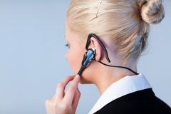 Woman talking on a headset with focus on headset Stock Images