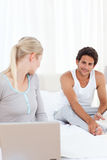 Woman talking with her boyfriend on the bed Stock Photography