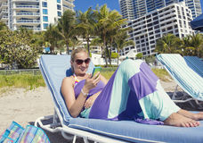 Woman talking on her cell phone while lounging on the beach Royalty Free Stock Photos