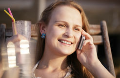 Woman talking on her mobile drinking cocktail and Royalty Free Stock Photography