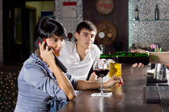Woman talking on her mobile phone in the pub. Woman chatting on her mobile while drinking at the bar in a pub sitting sideways at the counter listening to the royalty free stock photography