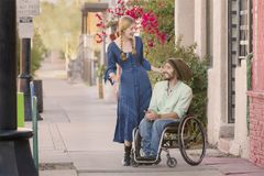Woman Talking with Man in Wheelchair. Woman having a conversation with friend in wheelchair on sidewalk Royalty Free Stock Photos