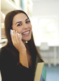 Woman talking on mobile and holding books Royalty Free Stock Images