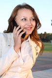 Woman talking on mobile phone. Nice woman talking on mobile phone at nature background stock image