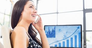 Woman talking on mobile phone against laptop in background Royalty Free Stock Images