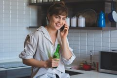 Woman talking on mobile phone and drinks beer royalty free stock images