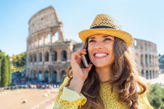 Woman talking mobile phone in front of colosseum Stock Photos