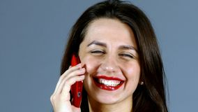 Woman Talking on Mobile Phone on grey background stock footage