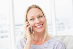 Woman talking on mobile phone in living room Royalty Free Stock Images
