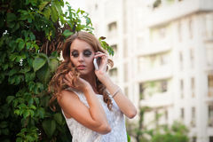 Woman talking on mobile phone, looking down. Outdo Stock Image
