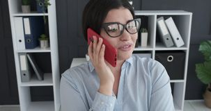 Woman talking on mobile phone at office. Young businesswoman talking on mobile phone at office stock video