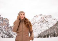 Woman talking mobile phone outdoors among snow-capped mountains Stock Photo
