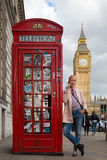 Woman talking on mobile phone, red telephone box and Big Ben. London, England Royalty Free Stock Images