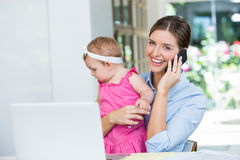 Woman talking on mobile phone while sitting with baby girl Stock Photos