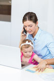 Woman talking on mobile phone sitting with baby girl Stock Photos