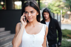 Woman talking on mobile phone and stalked by man criminal. Beautiful young women talking on mobile phone and being stalked by men criminal on the street stock photography