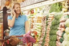 Woman Talking On Mobile Phone In Supermarket Stock Photography