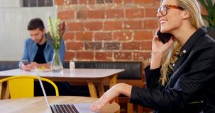 Woman talking on mobile phone while using laptop 4k. Woman talking on mobile phone while using laptop in cafe 4k stock video footage