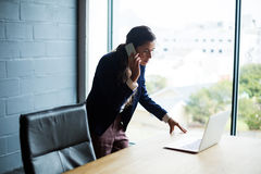 Woman talking on mobile phone while using laptop in office Royalty Free Stock Image