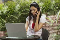 Woman talking on a mobile phone and using a laptop Royalty Free Stock Photos