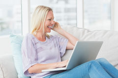 Woman talking on mobile phone while using laptop on sofa Stock Images