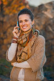 Woman talking mobile phone while walking in evening autumn park Stock Photos