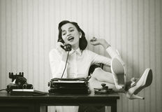 Woman Talking On Phone At Desk Stock Photography