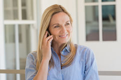Woman talking over phone. Cheerful mature woman talking over phone outdoor. Happy mid woman using mobile phone. Woman in a happy conversation through smartphone Royalty Free Stock Photo
