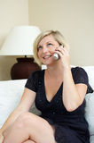 Woman talking on phone. Woman sitting on a sofa talking on a cordless phone Stock Photo