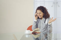Woman talking on the phone. Smiling woman with coffee and a book, sitting at a table and talking on the phone Royalty Free Stock Photos