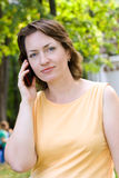 Woman talking on the phone. In the park stock photography
