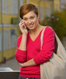 Woman talking on phone. Girl in pink blouse talking on the phone Stock Photos