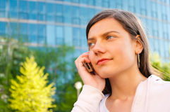 Woman talking on the phone. Portrait of a young woman talking on a mobile phone with modern building in background stock image