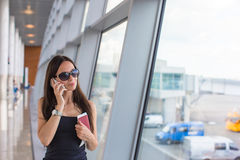 Woman talking by phone at airport waiting the Stock Photos