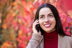 Woman talking on phone in autumn park Stock Images