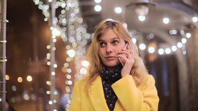 Woman talking on the phone on the background of night city stock video footage