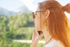 Woman talking on phone on background of summer mountains. Portrait of young woman talking on phone on background of summer mountains stock photos