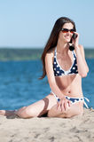 Woman talking by phone on a beach Royalty Free Stock Image