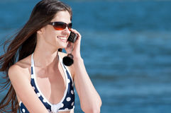 Woman talking by phone on a beach Royalty Free Stock Images