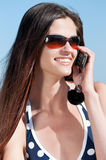 Woman talking by phone on a beach Royalty Free Stock Photos