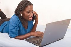 Woman talking on the phone in bed in front of a laptop stock photography