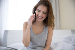 Woman talking on the phone in the bed Stock Image