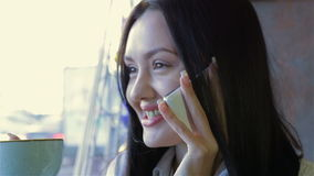 Woman talking on the phone in cafe stock footage