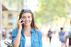 Woman talking on phone with copy space. Front view portrait of a happy woman walking towards camera talking on phone with copy space in the street Royalty Free Stock Photos